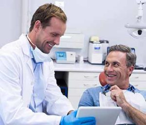 A denist is showing some images about dentures to a patient