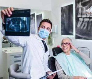 A dentist is showing an image to a patient