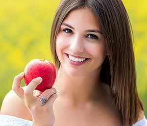 Image of a Young lady taking an apple