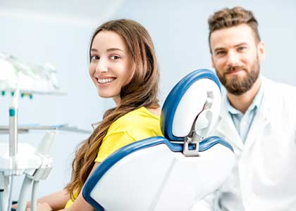 woman with toothy smile sitting at the dental chair with doctor on the background at the dental office